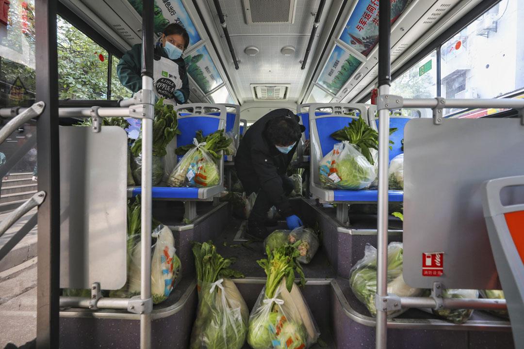 2020年3月5日,武漢,超市工作人員乘公車運送蔬菜給居民。
