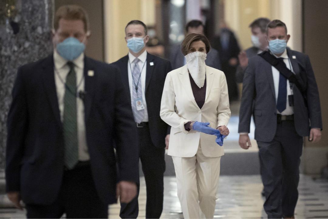 2020年4月23日,美國國會眾議長佩洛西(Nancy Pelosi)在回辦公室路上摘掉橡膠手套。 攝:Win McNamee/Getty Images