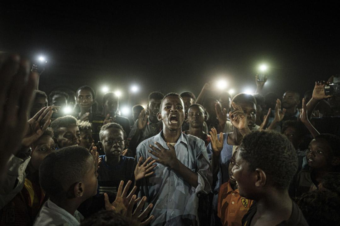 2019年6月19日,蘇丹喀土穆一次停電中,一位年輕示威者朗讀詩句,周圍的示威者則持手機燈光照亮並高喊口號。 攝:Yasuyoshi Chiba/AFP