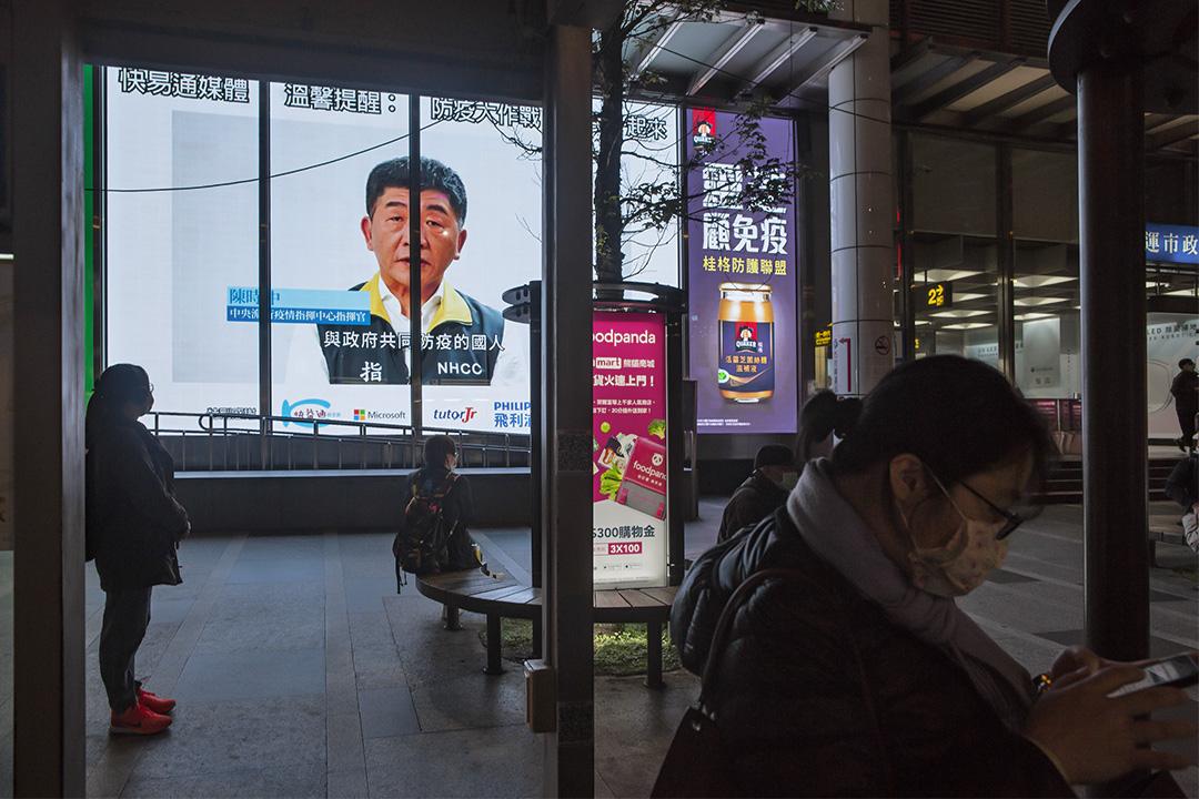 2020年4月7日,台北下班的市民在等候公車,螢幕上顯示中央流行疫情指揮中心指揮官陳時中講解的防疫宣傳。
