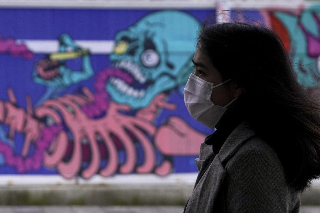 2020年2月13日,上海的一個建築工地前,一個戴著口罩的女人走過。