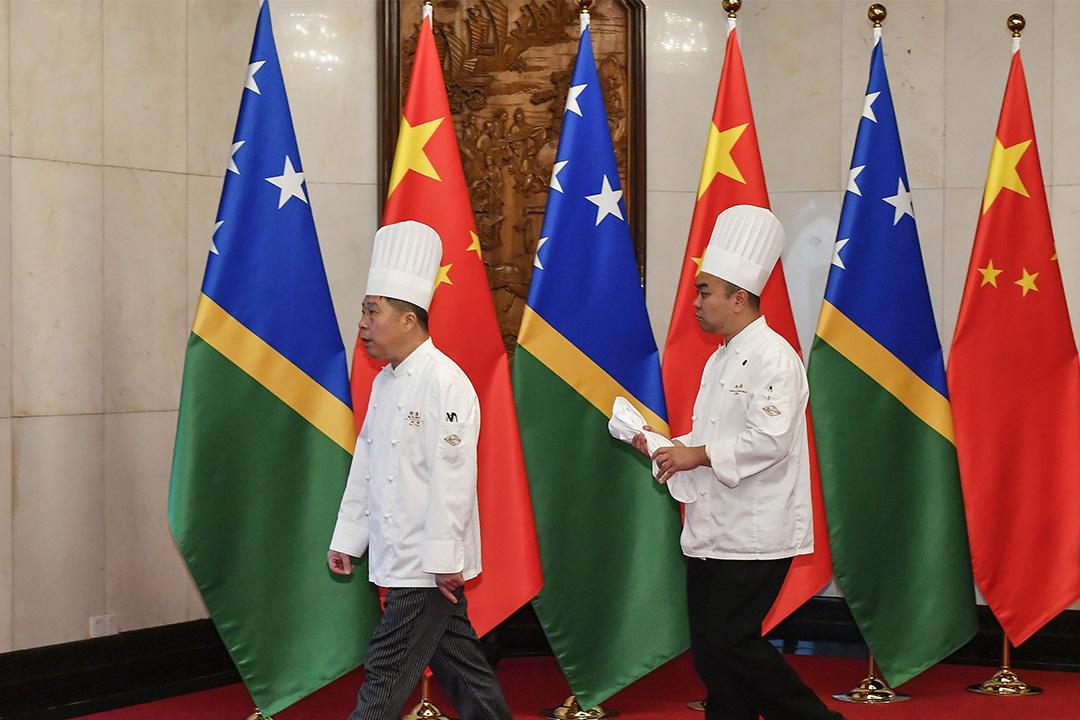 2019年10月9日北京釣魚台國賓館,中國國家主席習近平和索羅門群島總理梅納西·索加瓦雷會面前,二名廚師在索羅門群島和中國國旗前走過。