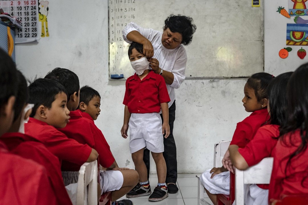 2020年3月4日,印尼一間幼兒園的老師向學生們展示如何佩戴口罩。 攝:Ulet Ifansasti/Getty Images