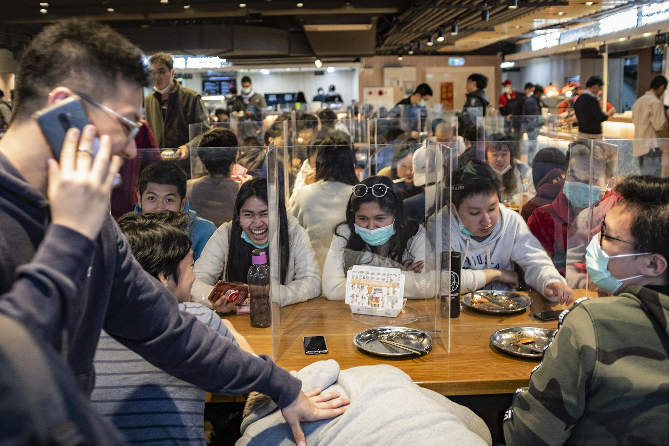 2020年3月6日,台灣台科大的餐廳內,學生們在用膠板分隔的餐桌上吃飯談天。 攝:陳焯煇/端傳媒