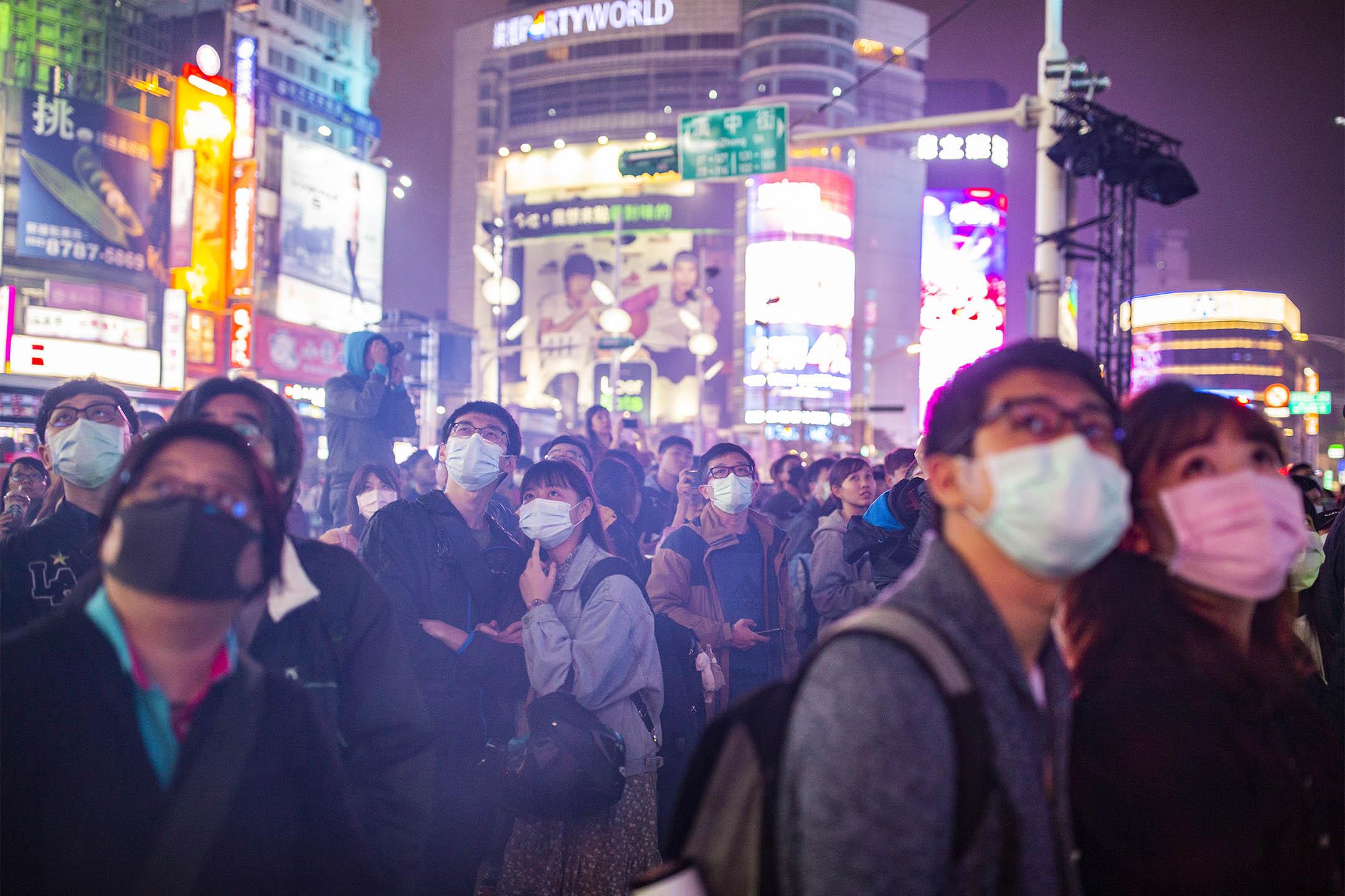 2020年2月14日情人節,市民戴上口罩在台北西門町欣賞燈飾。 攝:陳焯煇/端傳媒
