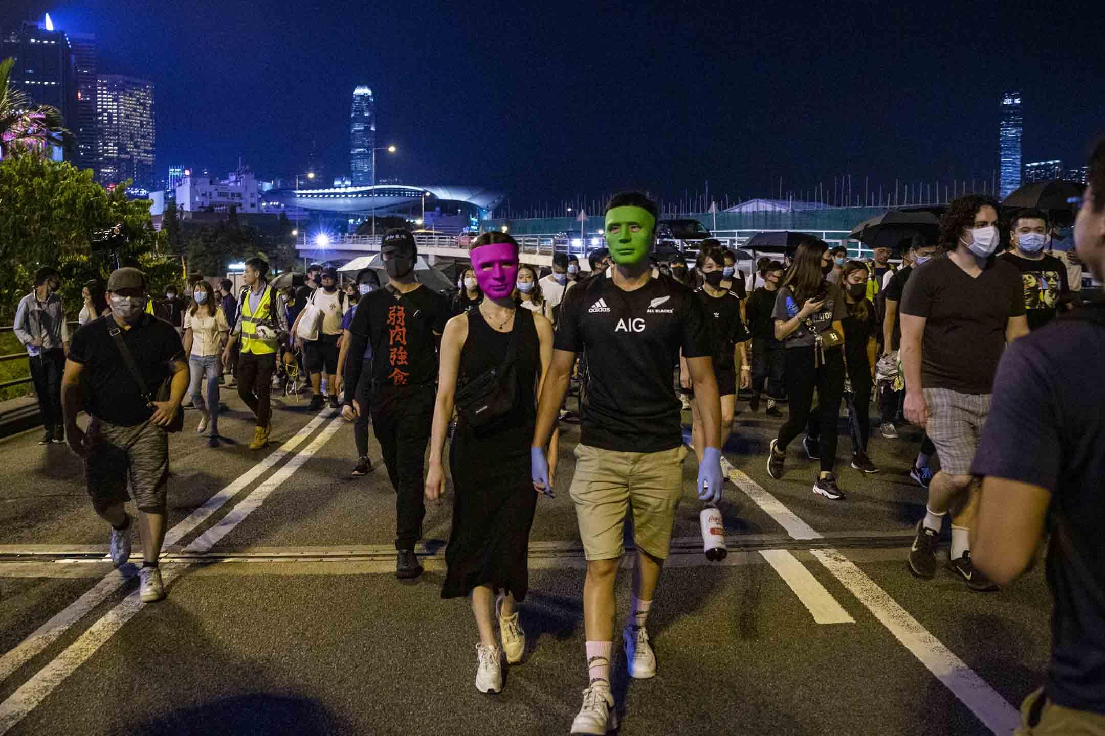 2019年10月4日,特首林鄭月娥聯同一眾問責官員召開記者會,宣布政府通過引用《緊急情況條例》訂立《禁止蒙面規例》, 晚上港島有市民戴上面具上街抗議。 攝:林振東/端傳媒