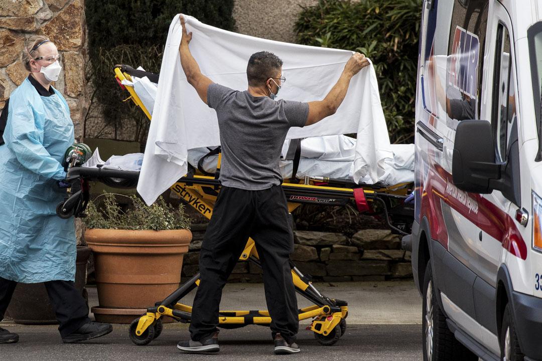 2020年2月29日,醫護人員將一位病人送上救護車,離開華盛頓柯克蘭的生命護理中心。 攝:David Ryder/Getty Images