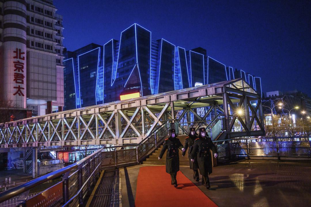 2020年2月16日中國,北京一個空蕩蕩的購物區,軍警戴著口罩巡邏。 攝:Kevin Frayer/Getty Images