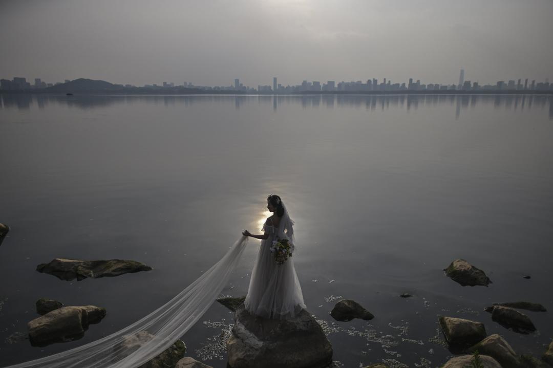 2020年4月19日,一位新娘在中國湖北省武漢市東湖旁拍攝婚紗照。 攝:Hector Retamal/AFP via Getty Images