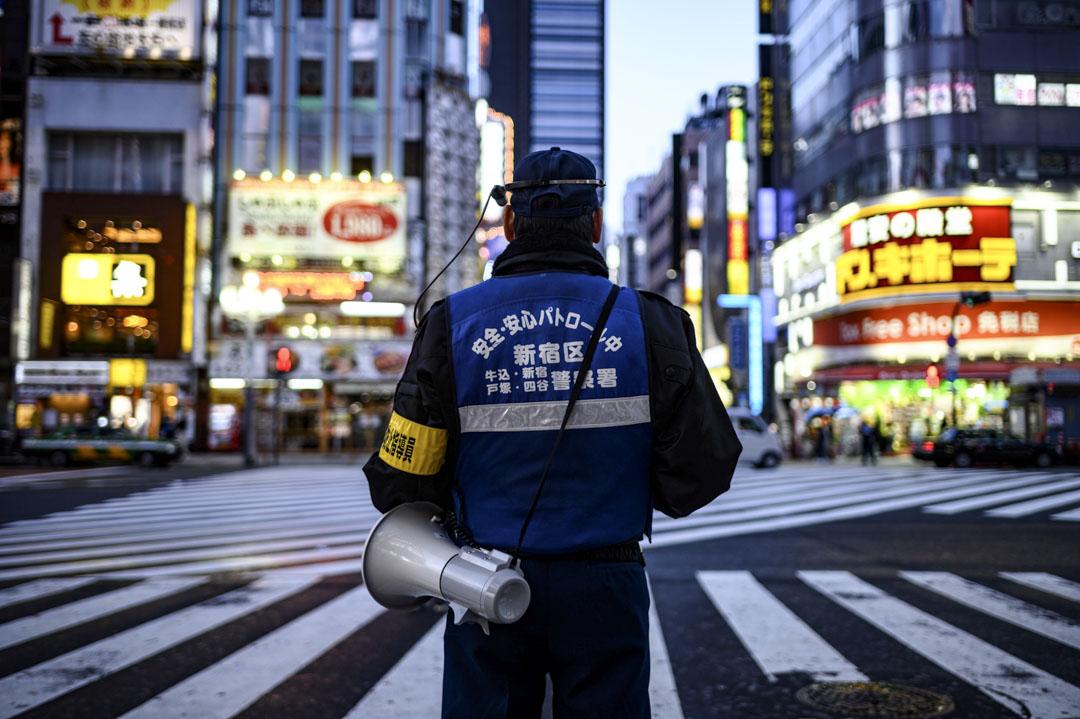2020年4月18日,日本東京一名警務人員帶著揚聲器,在新宿區的一個交通交匯點指揮交通。 攝:Philip Fong/AFP/Getty Images