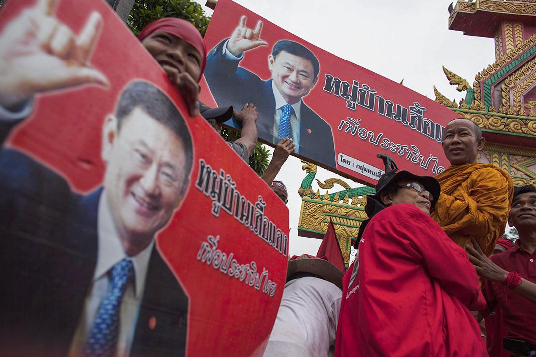 2011年6月25泰國烏隆他尼,紅衫軍支持者拿著被驅逐的總理他信的橫幅。