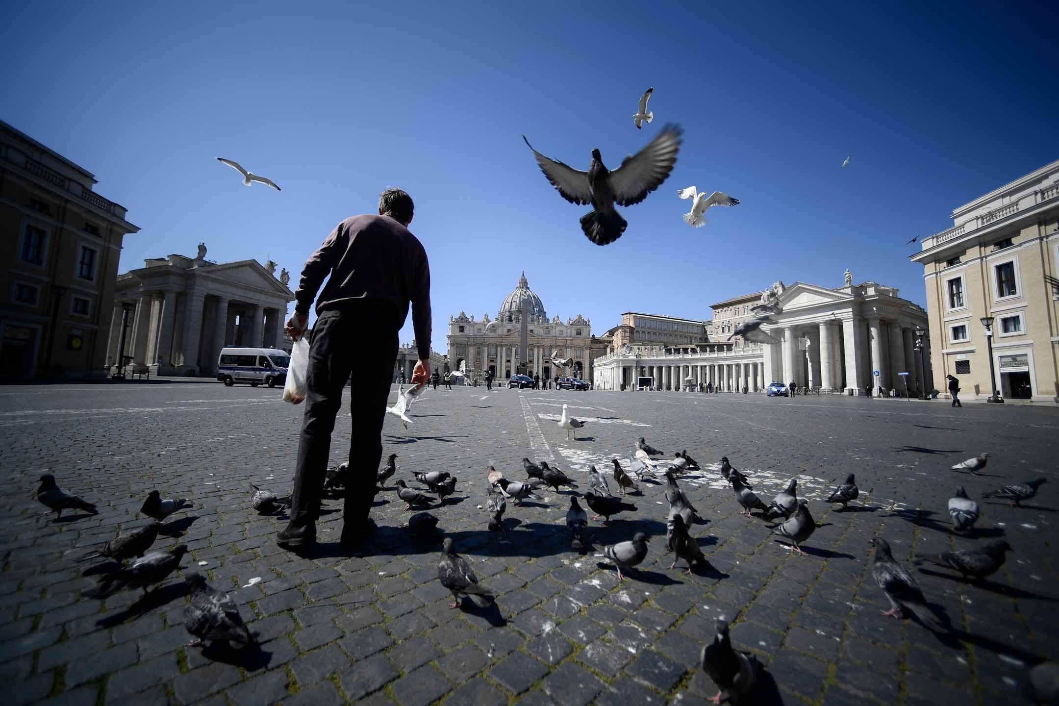 2020年3月25日,意大利在新冠狀病毒大流行後的封鎖期間,一名無家可歸的人餵鴿子。 攝:Filippo Monteforte/AFP via Getty Images