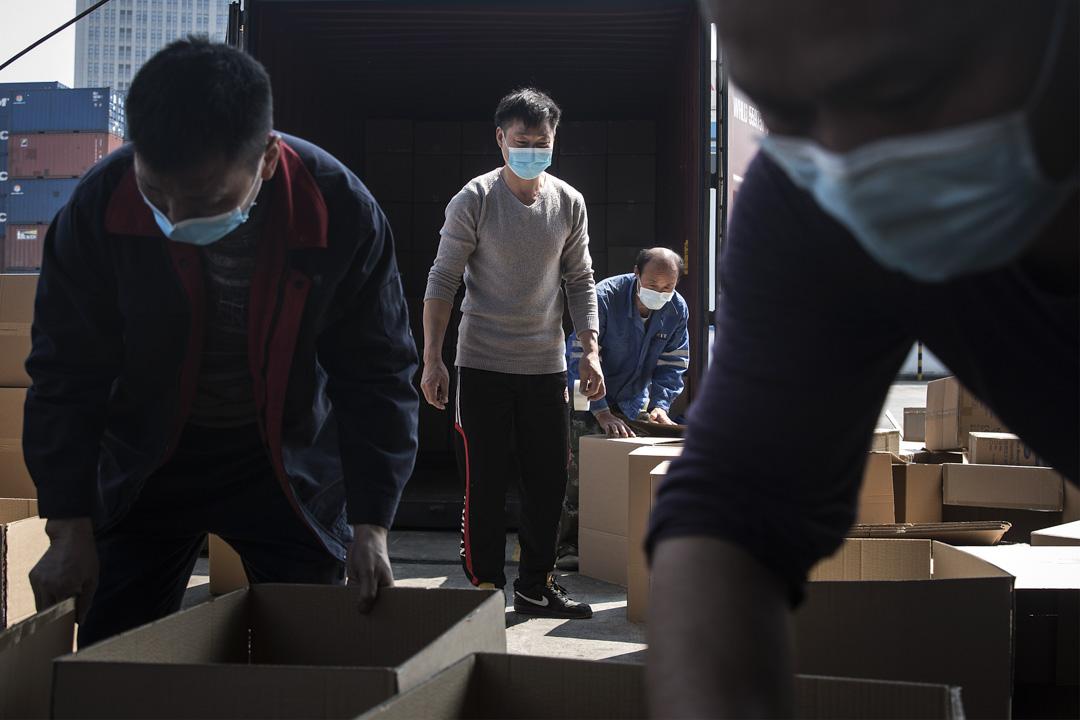 2020年4月12日,武漢市長江一個港口,工人搬運裝著口罩的貨箱。