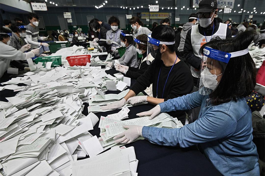 2020年4月15日,南韓選舉官員在首爾體育館舉行的議會選舉進行點票。