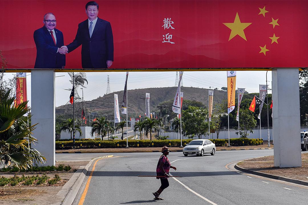 """2018年11月15日莫爾茲比港舉行的峰會,一名婦女在宣傳牌下過馬路,巴布亞紐幾內亞總理彼得奧尼爾與中國國家主席習近平握手,並寫上""""歡迎""""字樣。"""
