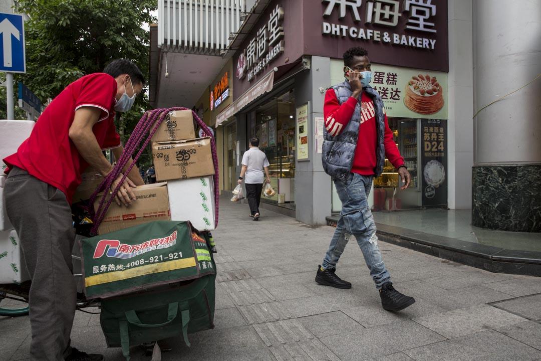 2020年4月18日,廣州大沙頭三馬路,一名行走在沿街店鋪旁的非裔居民。 攝影:禤灿雄