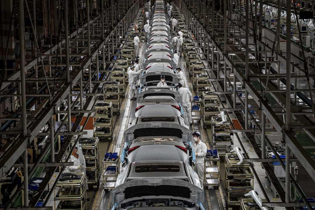2020年3月23日,戴著口罩的員工在湖北省武漢市的東風本田汽車廠的裝配線上工作。