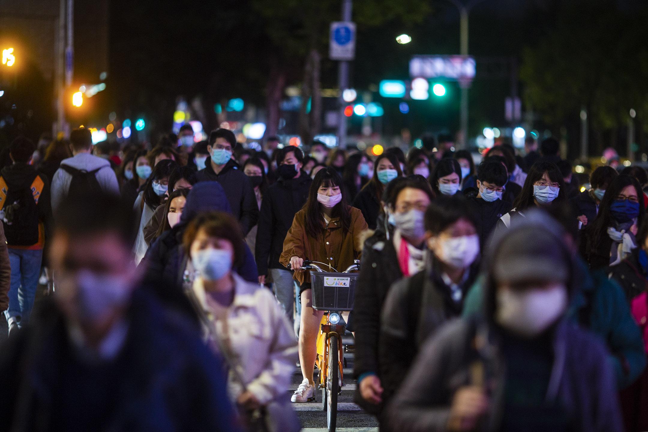 2020年4月7日,台北下班的市民戴上口罩走過馬路。