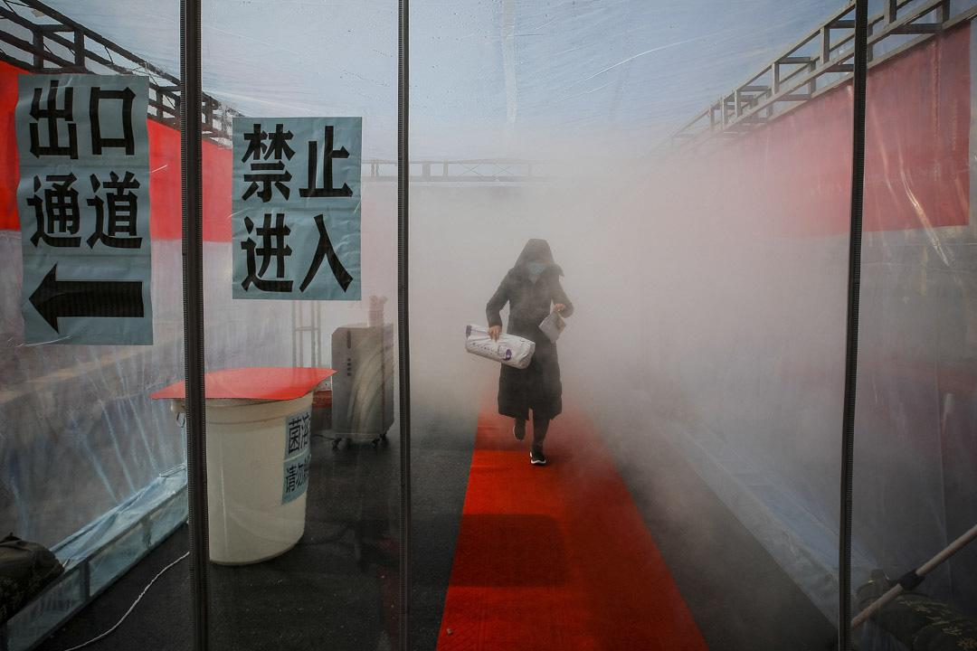 2020年2月11日中國天津,一名戴著口罩的婦女穿過消毒劑進入住宅大廈。