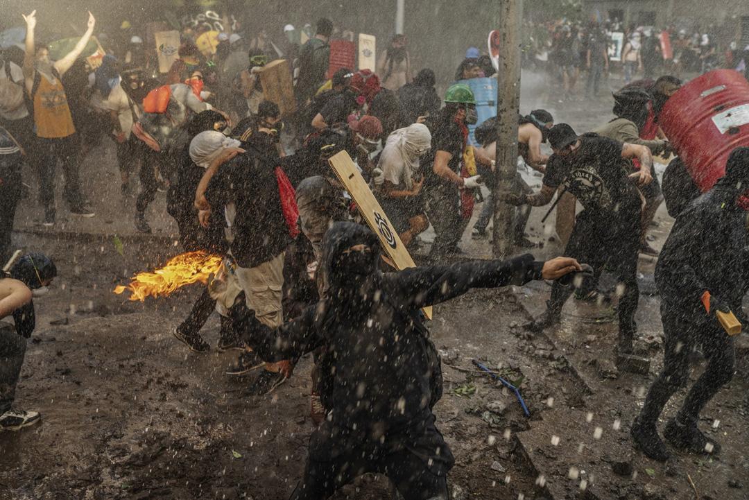 2019年12月13日,智利聖地亞哥的反政府示威者正在向警察投擲氣油彈。示威因為當地鐵路加價而引發,後來演變成要求大規模政府重整和經濟改革,控訴智利的貧富懸殊問題。