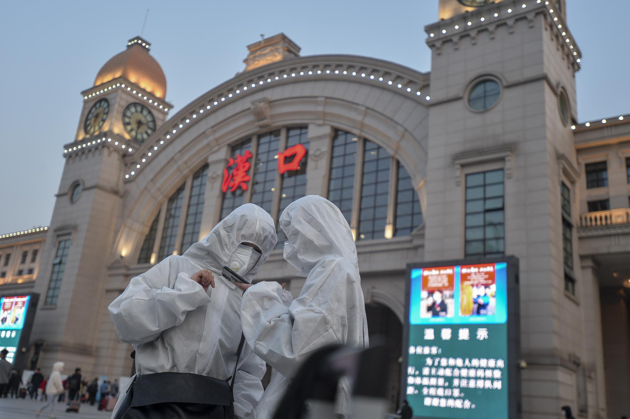 2020年4月8日,武漢解封第一天,兩名穿著防護衣的旅客在漢口火車站準備入站乘火車離開。 攝:Feature China/Barcroft Media via Getty Images