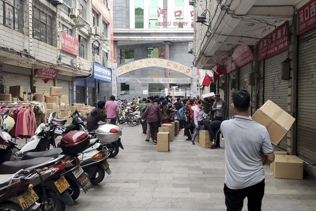 雲南紅河州河口縣的海關關口,人們排隊將口罩送向另一邊的越南。