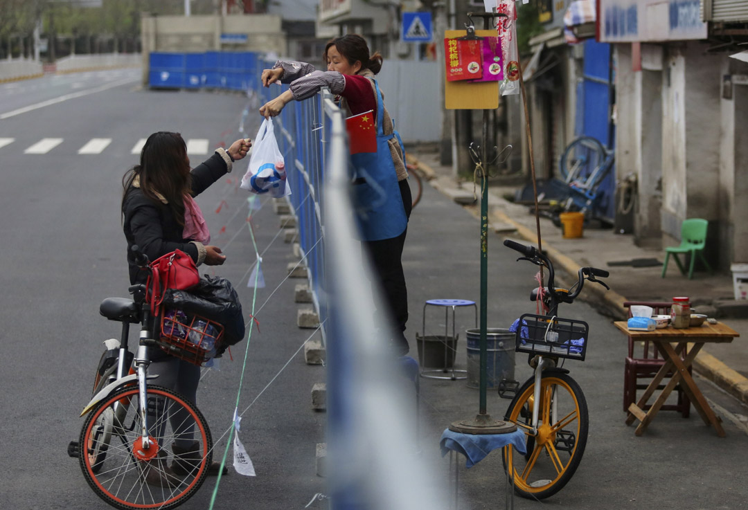 2020年3月16日,武漢,一名女士向屏障內的居民運送食物。