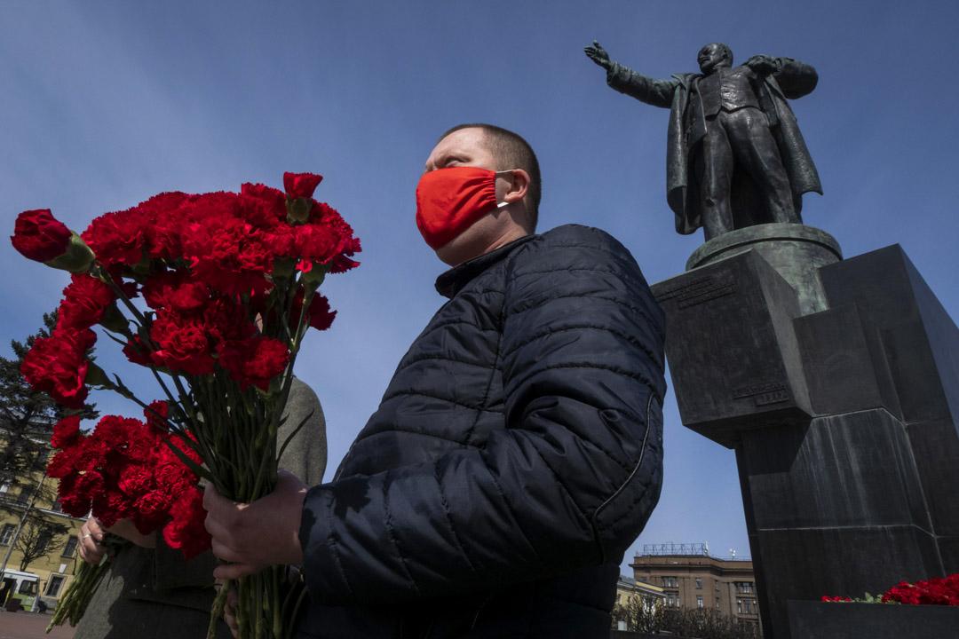 2020年4月22日,俄羅斯聖彼得堡慶祝其誕辰150週年的慶祝活動上,一名共產黨支持者戴著口罩,站在列寧的雕像旁邊。 攝:Dmitri Lovetsky/AP/達志影像