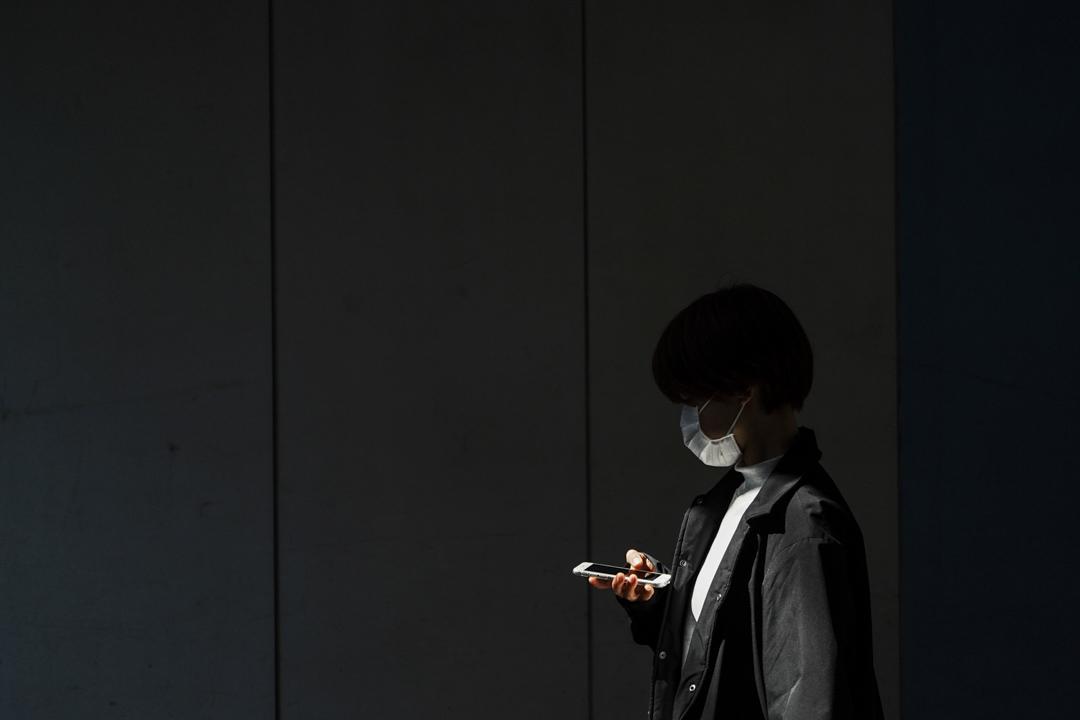 2020年4月6日,東京一名戴著防護口罩的女士走進的地下通道。