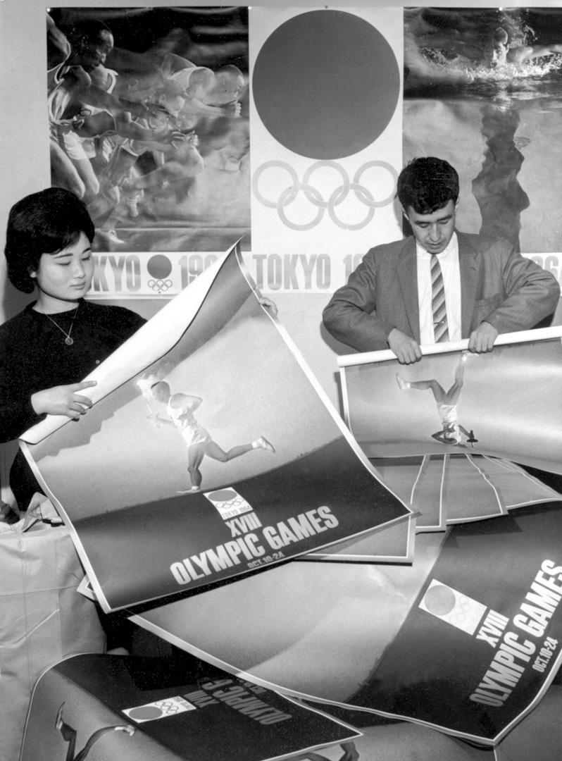 1964年5月,東京奧組委的工作人員滾動東京奧運會的海報。