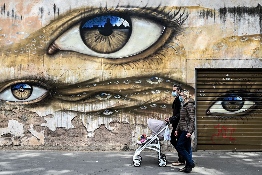 2020年4月13日,意大利羅馬,一對戴著口罩並推著嬰兒車的夫婦走過壁畫。