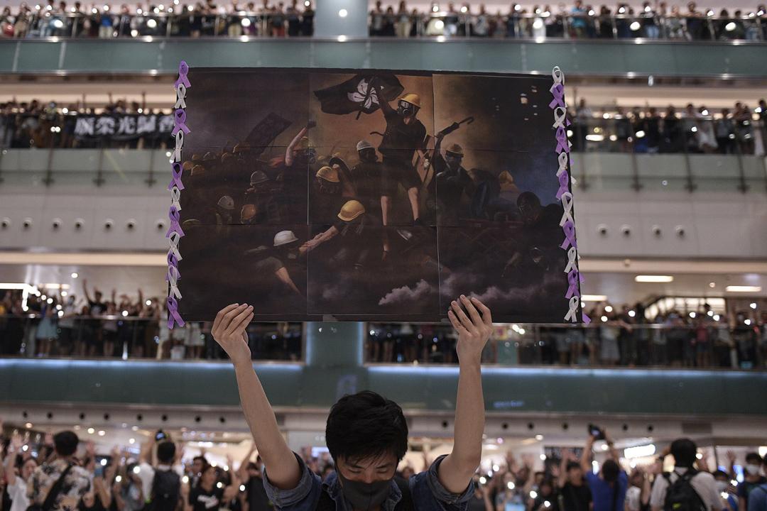 2019年9月11日,香港反修例運動示威者正在沙田新城市廣場內合唱《願榮光歸香港》,一名示威者舉起文宣海報。