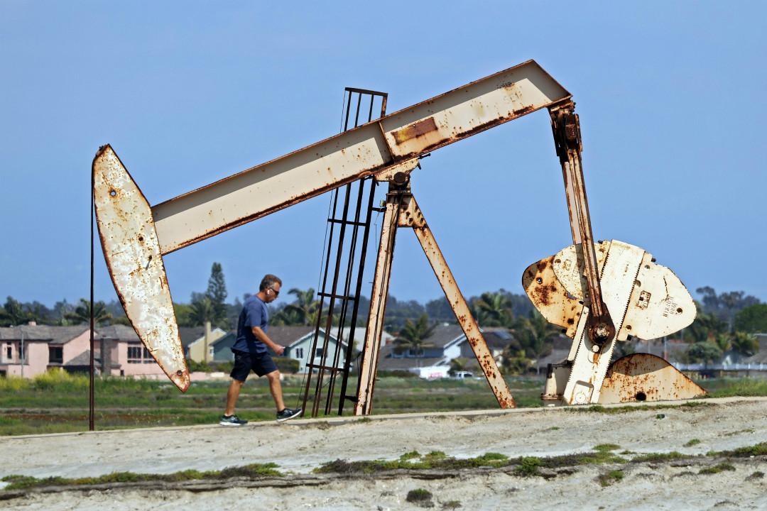 2020年4月20日,美國加州亨廷頓海灘油田附近,一名男子步行經過。 攝:Michael Heiman/Getty Images