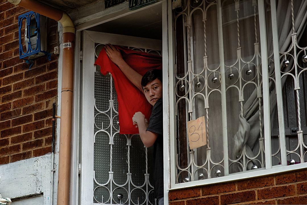 2020年4月22日哥倫比亞玻利瓦爾城,一個人在門前懸掛紅色的衣服。
