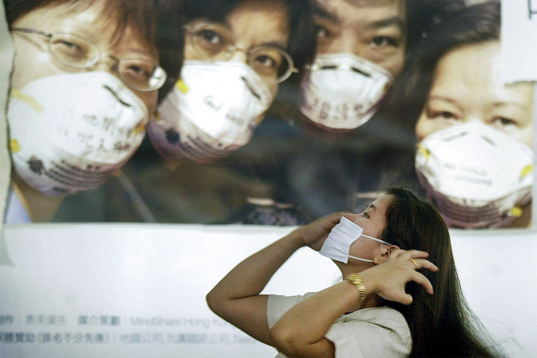 2003年4月27日,一名婦女戴上口罩,在敦促香港人戴口罩以預防SARS的海報旁。
