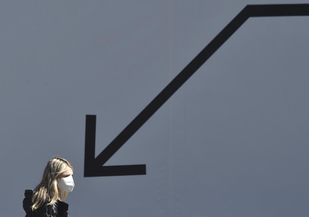 2020年4月6日烏克蘭首都基輔,一名戴著口罩的女子經過一塊廙告板。