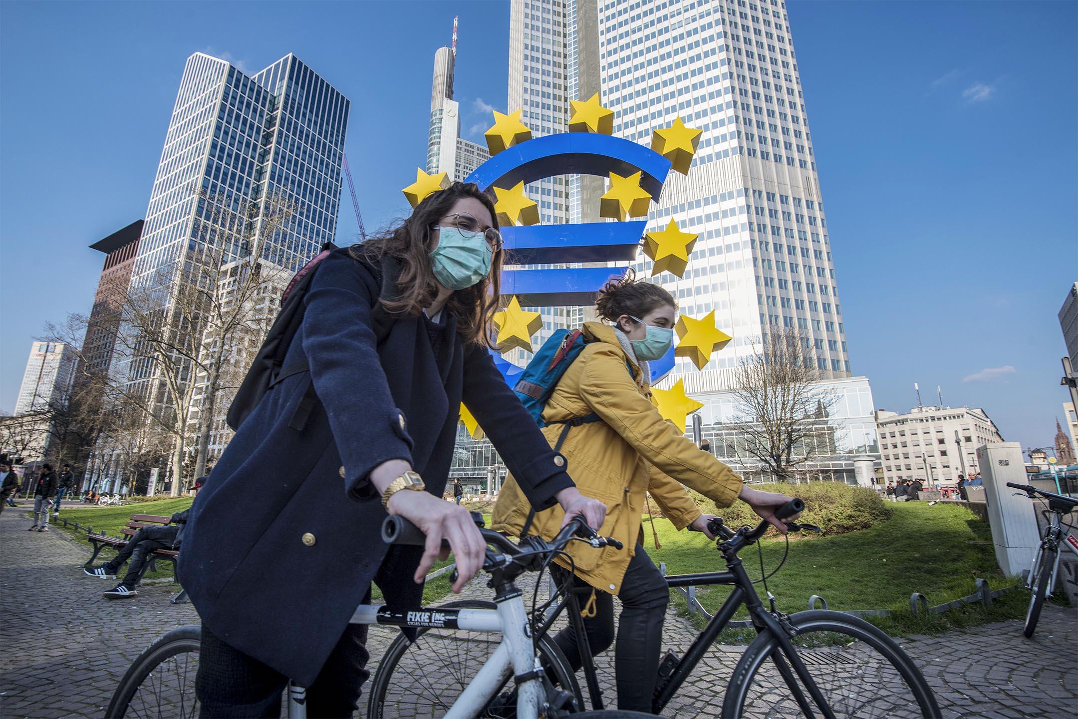 2020年3月19日德國法蘭克福,兩名學生戴著口罩騎自行車經過歐盟雕塑。 攝:Thomas Lohnes/Getty Images
