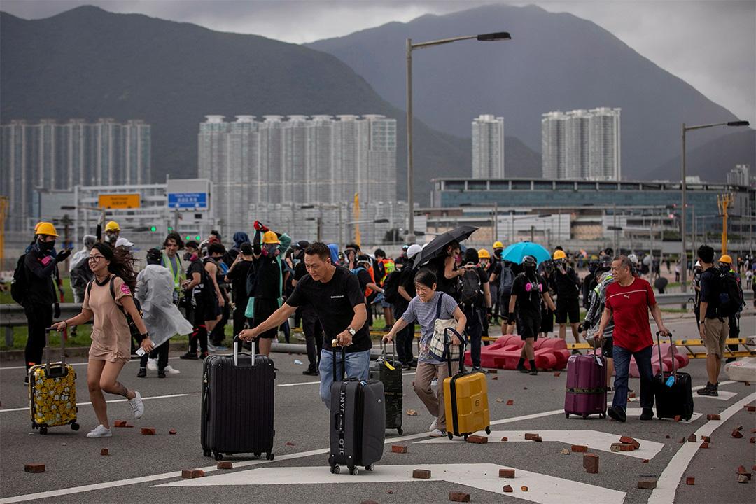 2019年9月1日,反政府示威者封鎖了通往香港國際機場的道路,乘客推著行李通過磚塊和障礙。