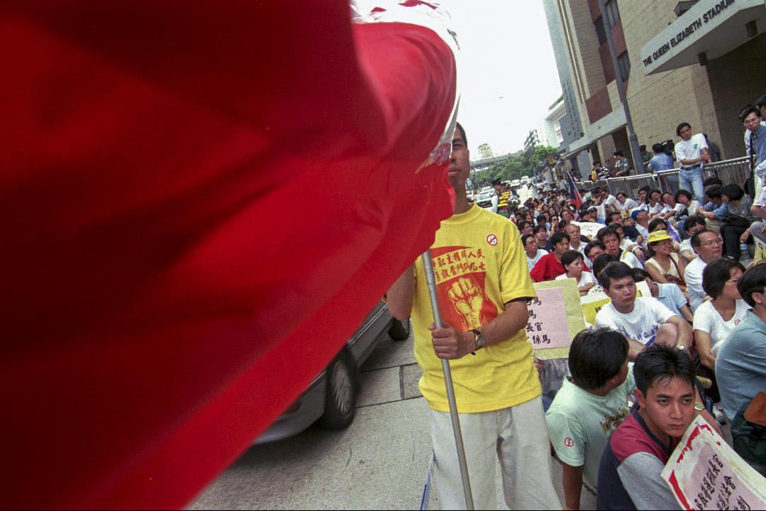 1996年6月30日,新華社香港分社外,示威者揮舞著紅色橫幅。