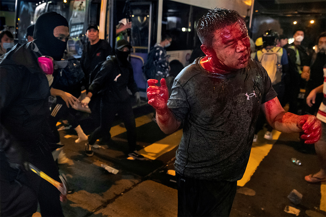 2019年11月11日,香港旺角的一場示威活動中,一名戴著面具的反政府示威者揮舞著錘子,襲擊了一名懷疑是來自中國大陸的親中旁觀者。