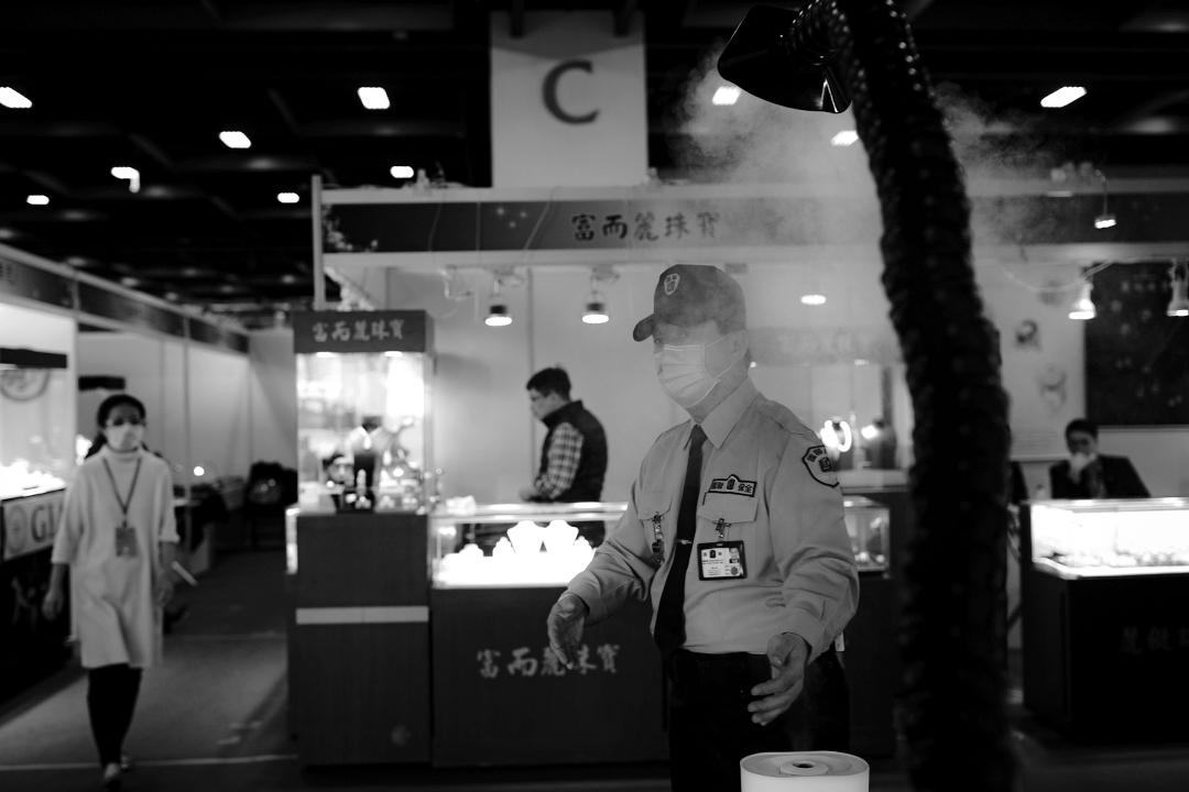 2020年2月21日台北,台北世貿中心珠寶展內的保安,以消毒噴霧機消毒。