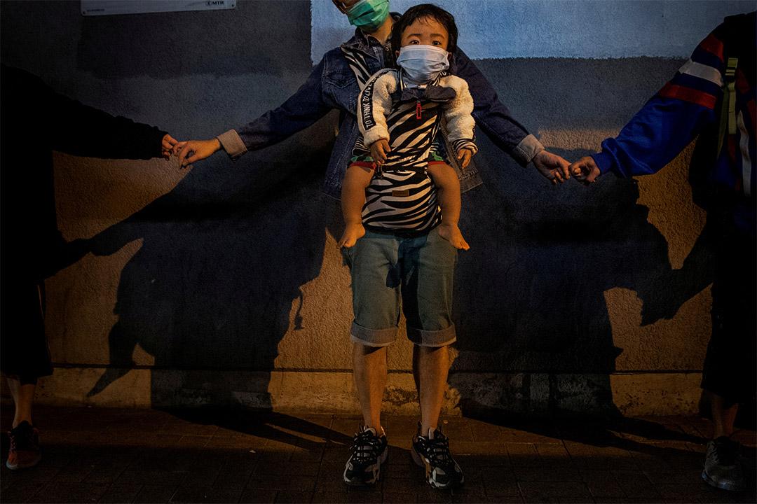 2019年11月30日香港九龍灣,反政府示威者牽著手形成人鏈,一個孩子戴著口罩在人鏈中。