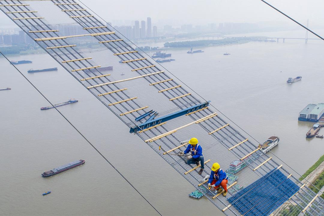 2018年5月8日中國湖北,工人在武漢市建造穿越長江的懸索橋。 圖:AFP via Getty Images