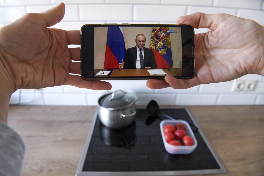 2020年3月25日莫斯科,一名婦女觀看俄羅斯總統普京就疫情發表講話的直播。
