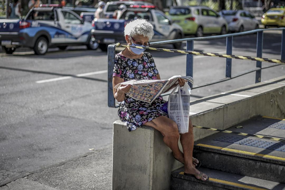 2020年5月13日巴西里約熱內盧,一名戴口罩的婦女在讀報紙。