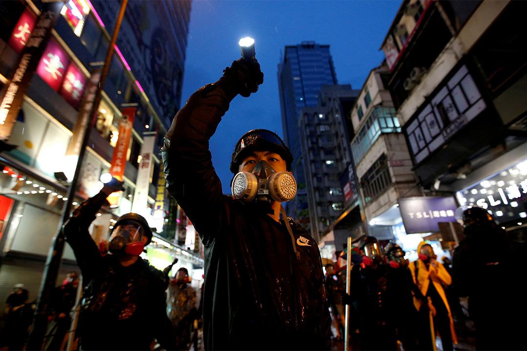 2019年8月25日,示威者於香港街頭被拘趕期間,將手電筒對準防暴警察。