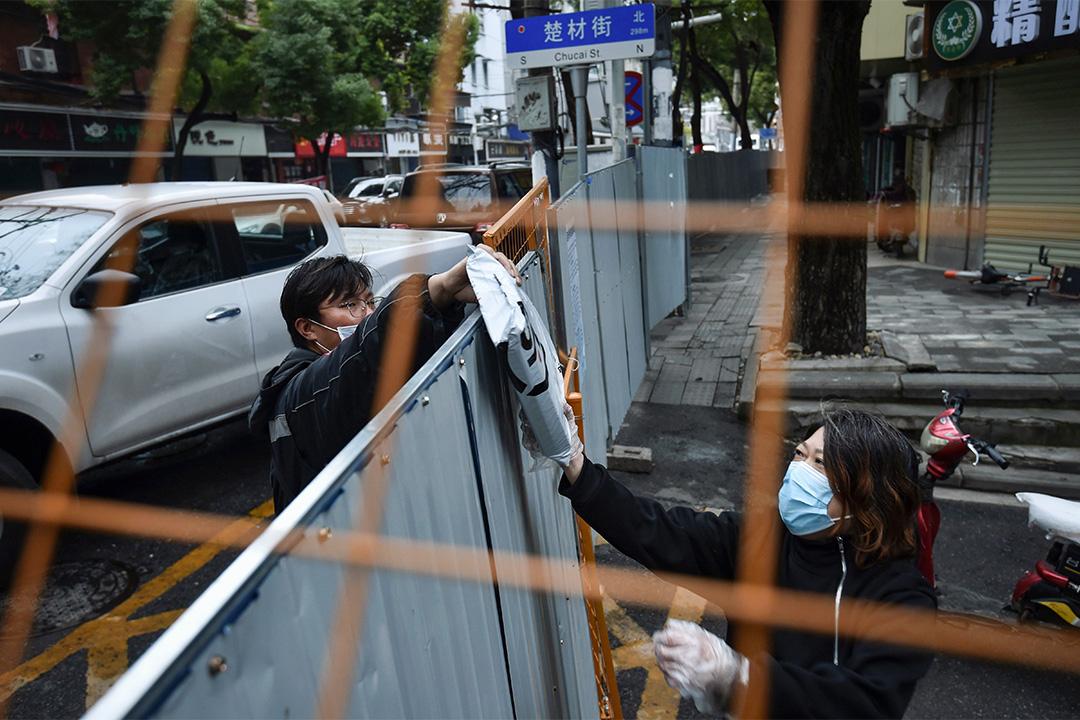 2020年2月26日湖北省武漢市,一名送貨騎手將包裹交給被隔離的居民,以預防2019冠狀病毒。