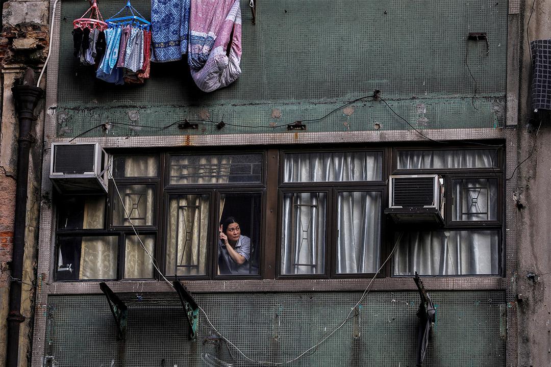 2019年10月20日,成千上萬的示威者於香港遊行時,一名婦女從住宅的窗戶望出去。