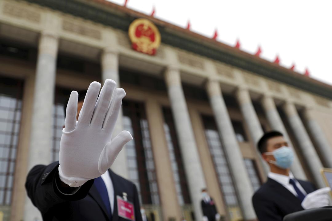 2020年5月21日,中國全國政協會議在北京揭幕,人民大會堂外一名保安人員伸手阻擋攝影鏡頭。 攝:Carlos Garcia Rawlins / Reuters