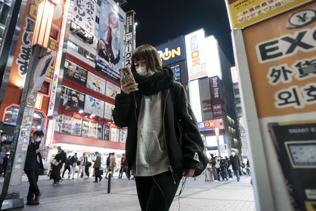 2020年2月13東京,戴著口罩的婦女使用智能手機。